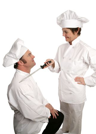 A humorous photo of a new chef being knighted by his cooking school instructor.  Isolated on white. photo