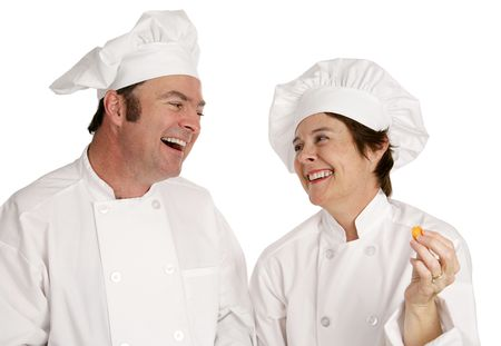 A male and female chef laughing together.  Isolated on white. photo