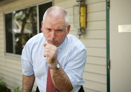A businessman coughing with a severe chest cold.   photo