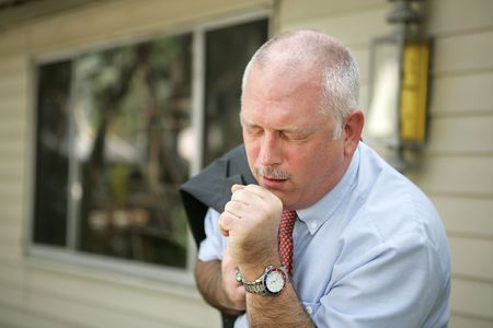 A mature man with a severe cough - probably the flu.   photo
