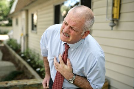 appears: A mature businessman doubled over clutching his chest. He appears to be having a attack. Stock Photo