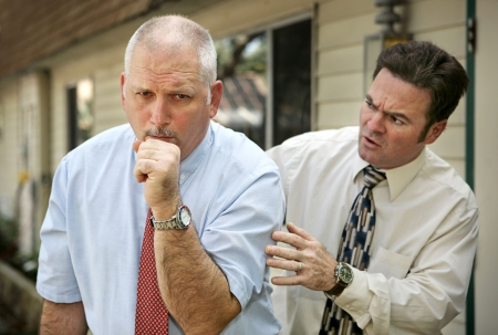 A mature businessman with a severe cough.  His worried colleague is patting him on the back.  Focus on coughing man.