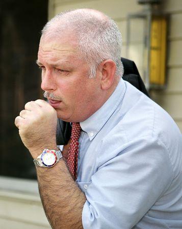 öksürük: A mature businessman with a severe coughing fit.