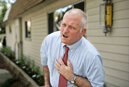 doubled: A mature businessman doubled over clutching his chest in pain.  Stock Photo
