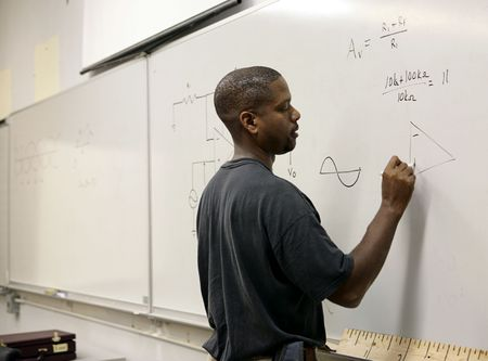 A handsome african-american student doing trigonometry at the board.   Stock Photo - 1193450