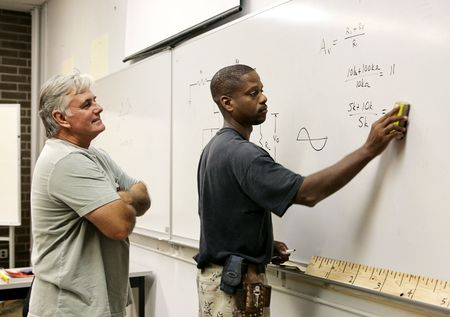 trigonometry: A teacher looks on as his adult education student erases the board.   Stock Photo