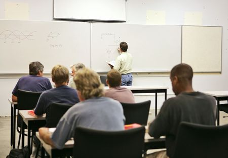 An adult education teacher in front of his class, drawing a diagram on the board.  Focus on teacher and diagrams.