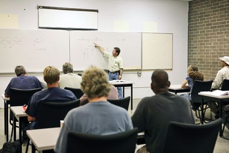 college classroom: An adult education teacher pointing to an electrical circuit on the board.  Focus on the diagram of the circuit.