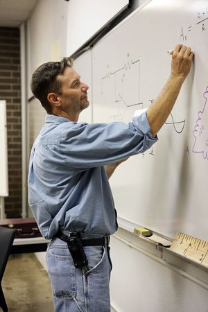 Handsome adult education teacher writing math problems on the board.  Vertical View Stock Photo