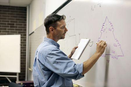 circuito electrico: Un guapo profesor de dibujo circuito el�ctrico en una pizarra.  Foto de archivo