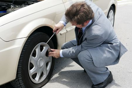 inconvenient: A businessman prying off the hubcap of his flat tire. Stock Photo