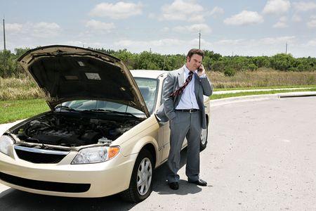 in trouble: Un hombre de negocios con un neum�tico desinflado en contacto telef�nico con el Auto Club.  Foto de archivo