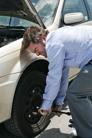 inconvenient: A businessman with a flat tire on the road strains to uncrew the lug nuts.   Stock Photo