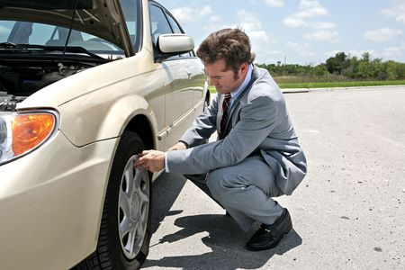 A businessman has a flat tire on the road.  Hes getting ready to change it.