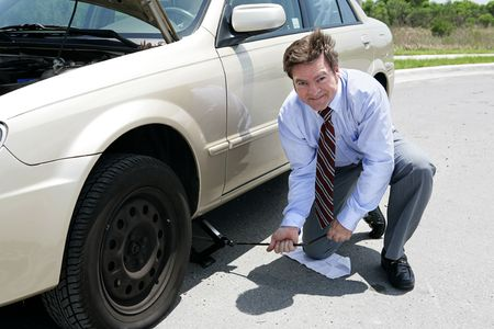 inconvenient: A businessman demonstrating how to use a jack to change a tire.