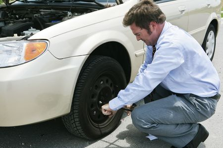 hubcap: A frustrated businessman loosening lug nuts on his cars flat tire. Stock Photo