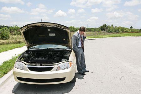 Een zakenman wiens auto is onderverdeeld in het midden van nergens. Hij belt de automatische club.