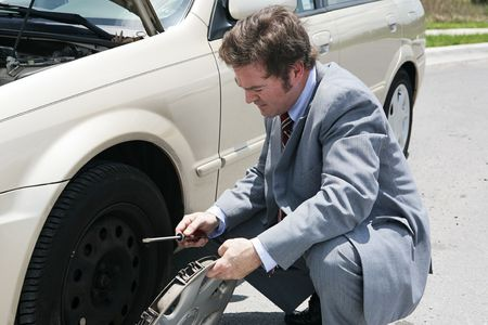 A businessman, stranded with a flat tire, removes his hubcap.