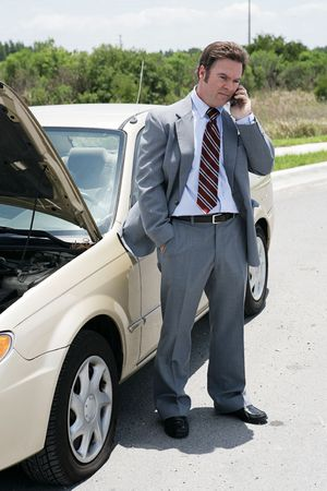 inconvenient: A businessman on the road with a flat tire.  Hes calling his next appointment to say he will be late.