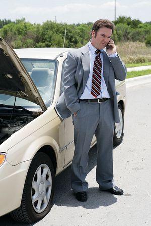llegar tarde: Un hombre de negocios en el camino con un neumático plano. He que llama su cita siguiente para decir lo será atrasado. Foto de archivo