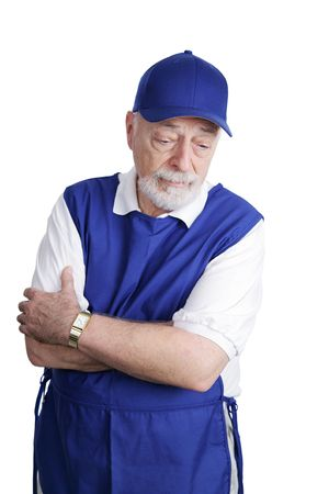 A senior man unable to retire is sad about working a menial service job.  Isolated on white.   photo