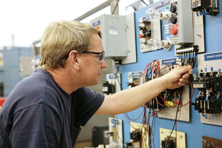depicted: A vocational education teacher wiring a motor control board.  All work depicted is accurate and being performed according to national code and safetly regulations.   Stock Photo