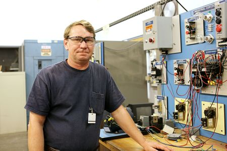 actual: An electrician in a technical education class standing beside a motor control training board. Actual electrician with real equipment according to national code and safety standards.