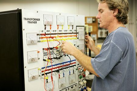 amperage: An adult education student learning electronics on a Transformer Trainer Board. Stock Photo