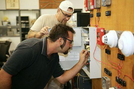직업 훈련 클래스에서 화재 경보 시스템을 연결하는 방법을 학습하는 전기 기사.