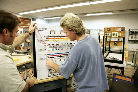 An adult education student learning about transformers.  Focus on the Transformer Trainer Board.