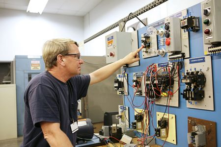 vocational high school: An electrical teacher working on an industrial motor control center in a classroom.   Stock Photo