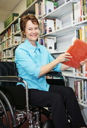 A pretty librarian in her wheelchair shelving books.   photo
