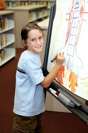 A cute school boy drawing a picture in class. Stock Photo - 1334300