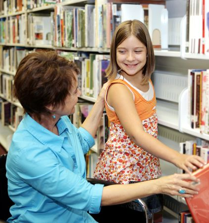 A librarian helps a child choose a book.  Shallow depth of field with focus on the little girl.   Stock Photo