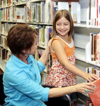 Un bibliothécaire aide un enfant choisir un livre. Faible profondeur de champ, l'accent étant mis sur la petite fille.