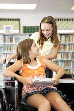 disabled person: Two school girls in the library - one is in a wheelchair.