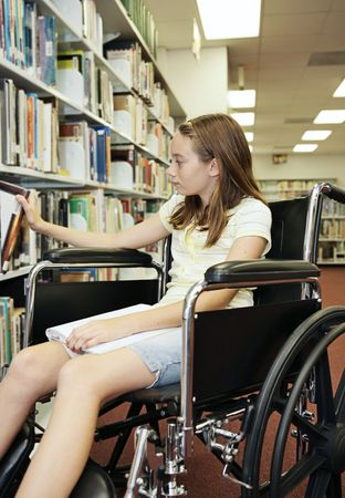 A young teen girl in a wheelchair selecting a book at the library.   Stockfoto