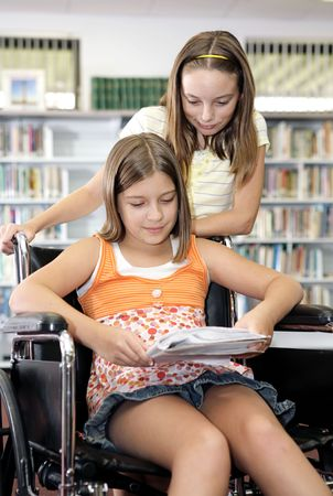 Two school girls reading notes in the library.  One is in a wheelchair.