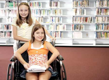 disable: Two school girls at the library.  One is in a wheelchair.