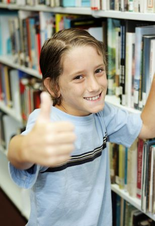 An adorable school boy at the library giving a thumbs-up.  Shallow depth of field. Stock Photo - 1334305