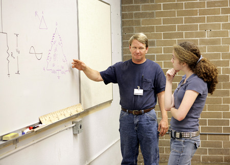 A high school teacher explains electrical theory to a vocational education student.