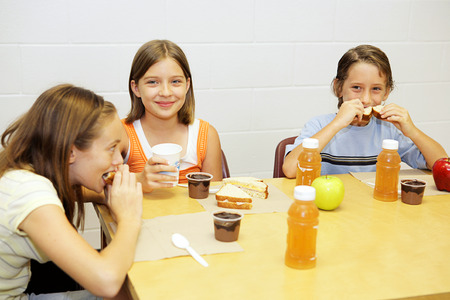having lunch: A group of school children having lunch in the school cafeteria. Stock Photo