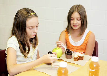 Two school girls eating lunch together in the cafeteria. Stock Photo - 1414431