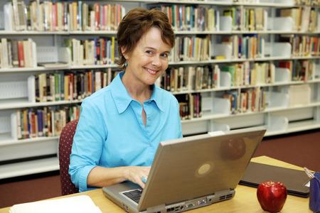 Une jolie bibliothécaire travaillant sur son ordinateur portable dans la bibliothèque de l'école.