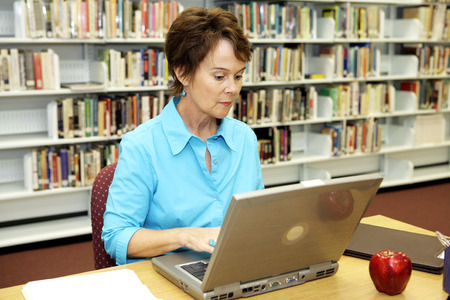 Een mooie school librarian doen researh online in de media center. Stockfoto