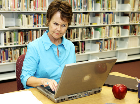 frowns: A school librarian frowns as she reviews students online activity.   Stock Photo