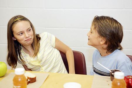 A school girl disgusted by her male classmate's eating behavior. Stock Photo - 1414424
