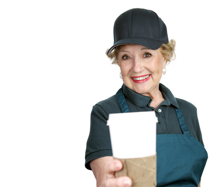 A pretty senior lady serving coffee with a smile.  Isolated with room for text. photo
