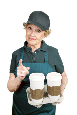 A senior worker in a coffee shop angrily confronting a difficult customer.   photo