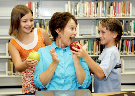 Two students giving apples to their favorite teacher.  She is very surprised and happy. Stock Photo